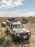 Safaris car with tourist. Taking photos in the serengeti with clouds in the sky, you can see some mountains. It´s a vertical picture Royalty Free Stock Photos