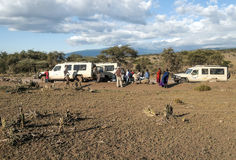 Safaris cars. With tourist in the serengeti with clouds in the sky, you can see some mountains Royalty Free Stock Image