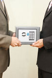 Safe. Two businessmen holding a steel safe Stock Photography