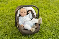 Baby in car seat on grass Royalty Free Stock Image