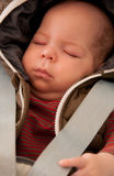 Safe baby sleeping. A baby boy sleeping in a car with safety belts Royalty Free Stock Image