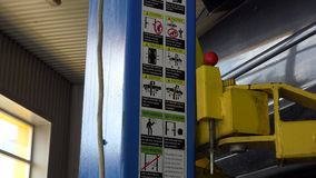 Safe car lift elevator in garage and safety pictures and instructions. Safe car lift elevator and safety pictures and instructions in garage. Zoom out stock video