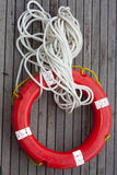 Safe circle with rope. Safe support  circle with rope. Rescue water red life buoy on wooden background of ship or boat. Helpful object Stock Photos