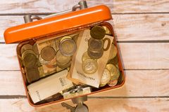 Safe with coins. On top of a wooden board Royalty Free Stock Images