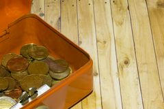 Safe with coins. On top of a wooden board Royalty Free Stock Photography