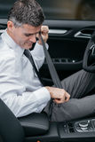 Safe driving. Businessman in his car fastening the seatbelt, safe driving concept Stock Image