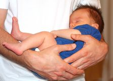 Safe in father's arms. Baby boy sleeping peacefully in daddy's arms Royalty Free Stock Images