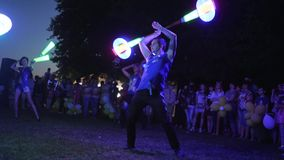 Safe fire show in dark in park, bright Lights In arms of girls and guys in nature, Holiday of fire, LEDs art For people. Kherson, Ukraine - 8 July 2017: Festival stock video