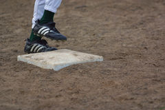Safe at First. Little league players feet arriving at first base Royalty Free Stock Photography