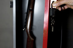 Safe With A Gun. Human hand opening a metal safe with a gun inside, studio cropped shot Stock Images