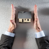 Safe home concept with straight businessman hands protecting new house Stock Photography