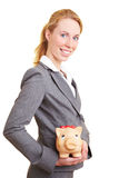 Safe investment. Businesswoman holding a big piggy bank in her hands royalty free stock photo