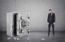 Safe with its door broken open and disappointed businessman full height Stock Photography