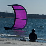 Safe Kite surfer sitting on the beach Stock Image