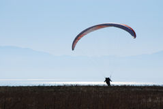 Safe Landing. Silhouette of a paraglider landing safely on the ground in the morning light Royalty Free Stock Photos