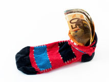 Safe money. Money saved at home in old red-blue-black sock isolated Royalty Free Stock Images