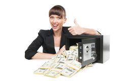 Safe with money. Happy young businesswoman in formalwear sitting at the table near the safe full of money while isolated on white Royalty Free Stock Photo