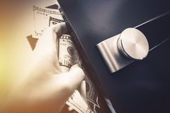 Safe Money Hiding. Closeup Photo. Hand Full of Cash Trying to Push Money Into the Safe Royalty Free Stock Photography