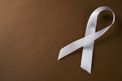 Safe motherhood. White awareness ribbon on brown background. Symbol of anti violence against women, safe motherhood. Top vew with copy spaced Stock Images