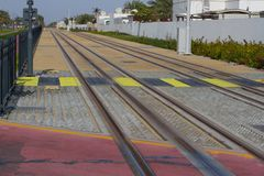 Safe passage through rails at a tram stop in Dubai. Railway pedestrian crossing. Colored zebra. Safe passage through rails at tram stop in Dubai. Railway Stock Photo