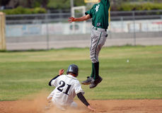 Safe on Second Base. Runner safe on second as second baseman jumps to catch ball stock photography
