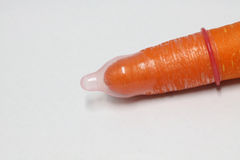 Safe sex. Carrots and condom Royalty Free Stock Photo