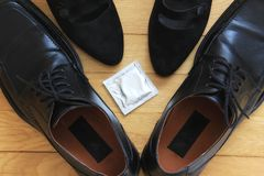 Safe sex. A concept of safe sex; man shoes, woman heels and a condom Royalty Free Stock Photos