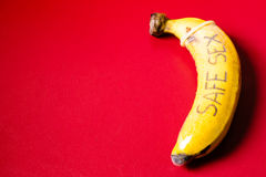 Safe sex concept of condom on banana. With red background royalty free stock images