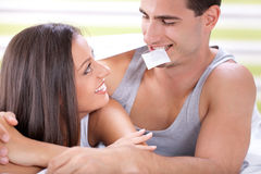 Safe Sex. Young attractive couple in bed with a condom Royalty Free Stock Photography
