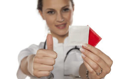 Safe sex. Young woman doctor holding condoms and showing thumb up Stock Photos