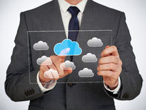 Safe storage on cloud. Businessman touching a virtual screen with clouds icons Stock Images