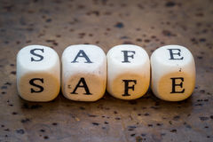 Safe. Text on wooden cubes on a brown cork background stock images