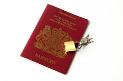 Safe travel. UK Passport and padlock on white Royalty Free Stock Images