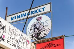A sign on the minimarket with a painted Religious Jewish Superman with the sign of the city of Safed on his chest in the artists q. Safed, Israel, September 08 royalty free stock photo