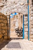 Safed street, bystreet, alley, backstreet with benches, ancient stone walls, arcs and blue white decorations. Safed Old Town street, bystreet, alley, backstreet stock photography
