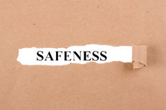 Safeness. Word safeness appearing behind torn brown paper Stock Images