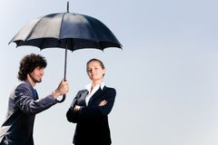 Safety. Image of confident business man holding umbrella and looking at woman on the background of sky Royalty Free Stock Photos