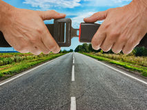 Safety belt on the background of the road. Hands button safety belt on the background of the road Stock Photos