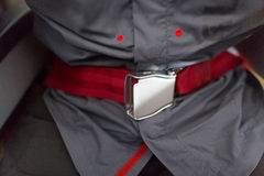 Safety belt. Red safety belt in the airplane Royalty Free Stock Photos
