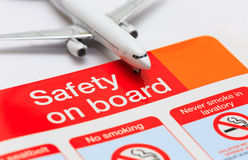Safety on board. Concept for airline safety. Detail of model airplane on safety instruction card found in the seatback pocket of all airliners Stock Photos