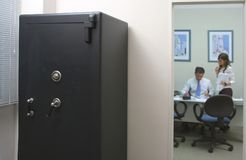 Safety box in an office with an employee and his secretary. Concept os security stock photo