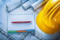 Safety building helmet checked notebook pen blueprints on constr. Uction plan royalty free stock images