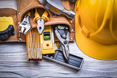 Safety building helmet toolbelt on wooden board construction con. Cept Royalty Free Stock Images