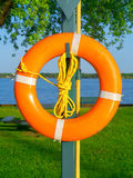 Safety buoy. An orange safety buoy with rope on a post at near a waterway Royalty Free Stock Image