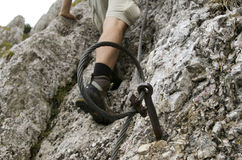 Safety cable on hiking mountain trail. Men with boot ascending on the limestone rock Royalty Free Stock Photo