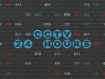 Safety concept: CCTV 24 hours on wall background. Safety concept: Painted blue text CCTV 24 hours on Black Brick wall background with Binary Code Stock Images