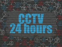 Safety concept: CCTV 24 hours on wall background. Safety concept: Painted blue text CCTV 24 hours on Black Brick wall background with Scheme Of Hexadecimal Code Stock Images
