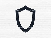 Safety concept: Contoured Shield on wall background. Safety concept: Painted black Contoured Shield icon on White Brick wall background Royalty Free Stock Photos