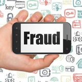 Safety concept: Hand Holding Smartphone with Fraud on display Stock Image