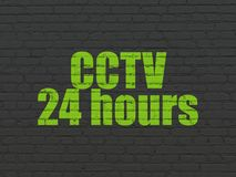 Safety concept: CCTV 24 hours on wall background. Safety concept: Painted green text CCTV 24 hours on Black Brick wall background Royalty Free Stock Photo